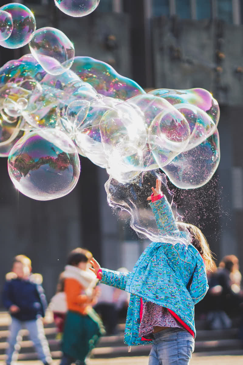 Child playing with bubbles outside