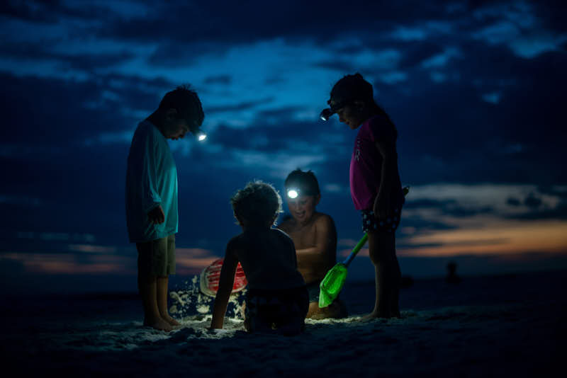 kids with headlights digging in the sand at the beach