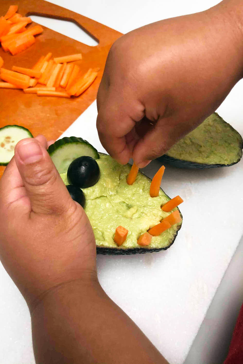 Healthy Veggie Dip - Hummus and Guacamole dip being assembled by kid into crocodile shape