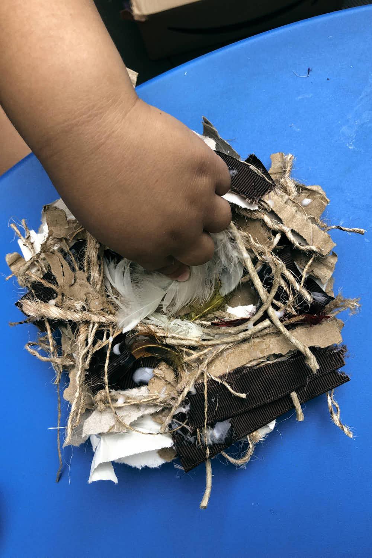 Bird Nest Craft - made by preschooler, gluing cardboard and string