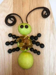 Bug themed food - this healthy snack idea uses apples, blueberries, grapes - finished insect overhead shot