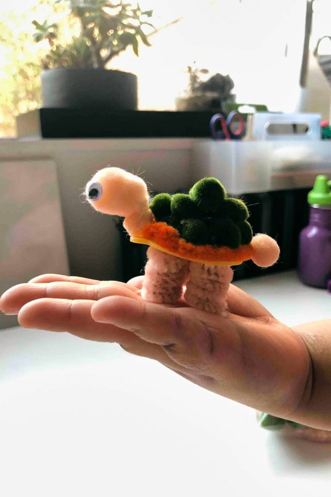 Easy Pom Pom Pom Craft for Kids - Turtle - finished being held by kid