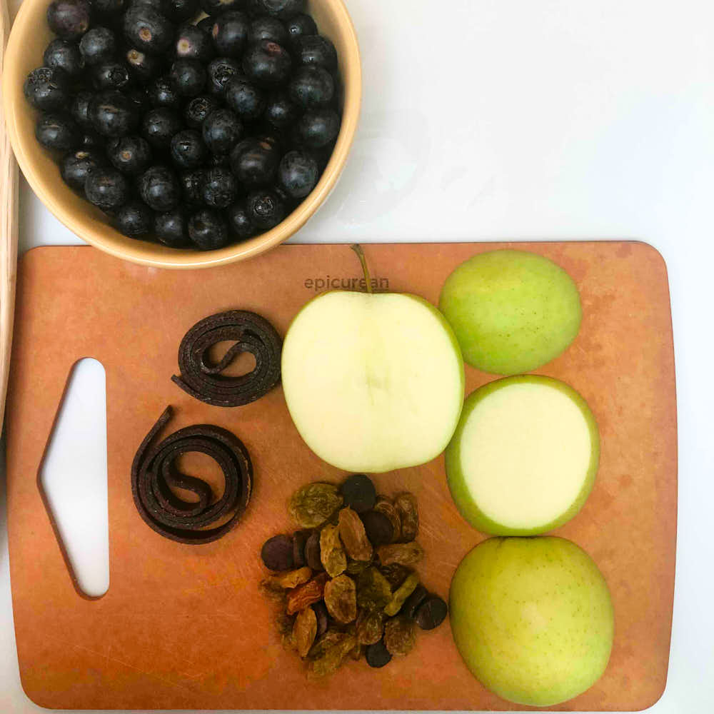 Ingredients needed for this bug theme snack activity - showing apples, grapes, blueberries