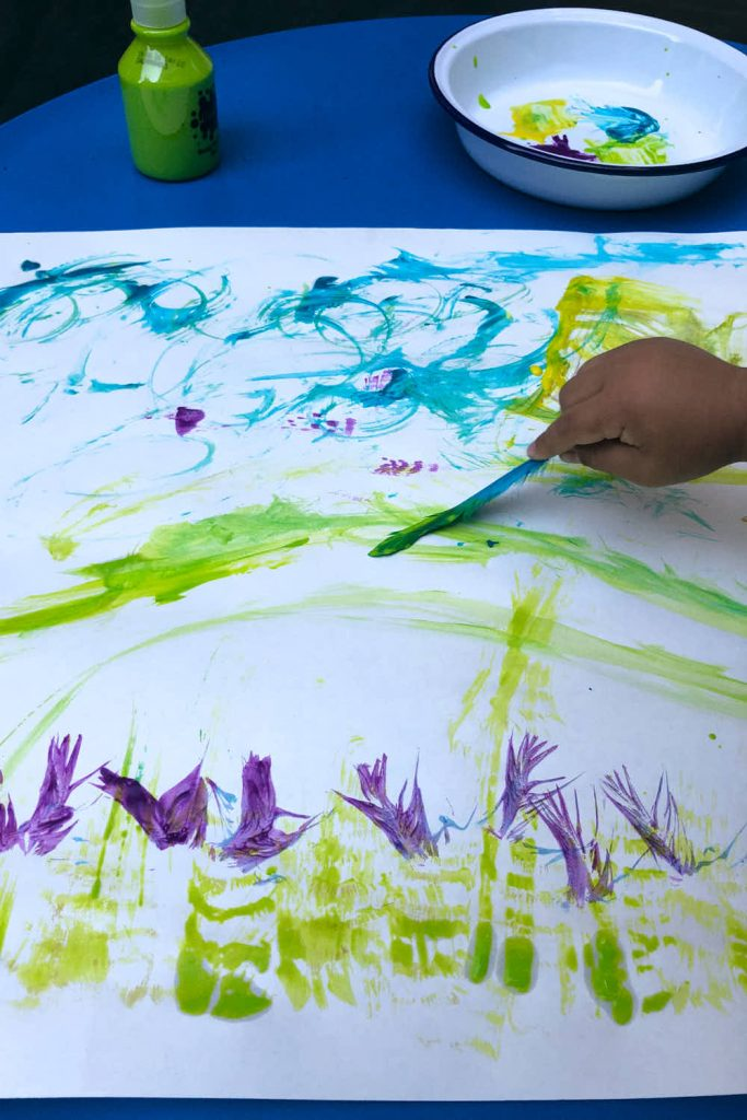 kid using feather to paint art and craft